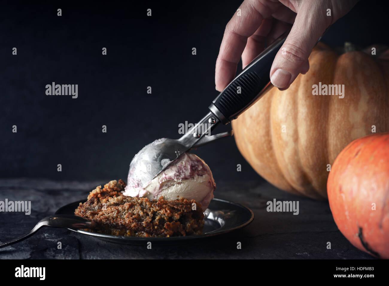 Putting ice cream on the pumpkin dump cake - Stock Image