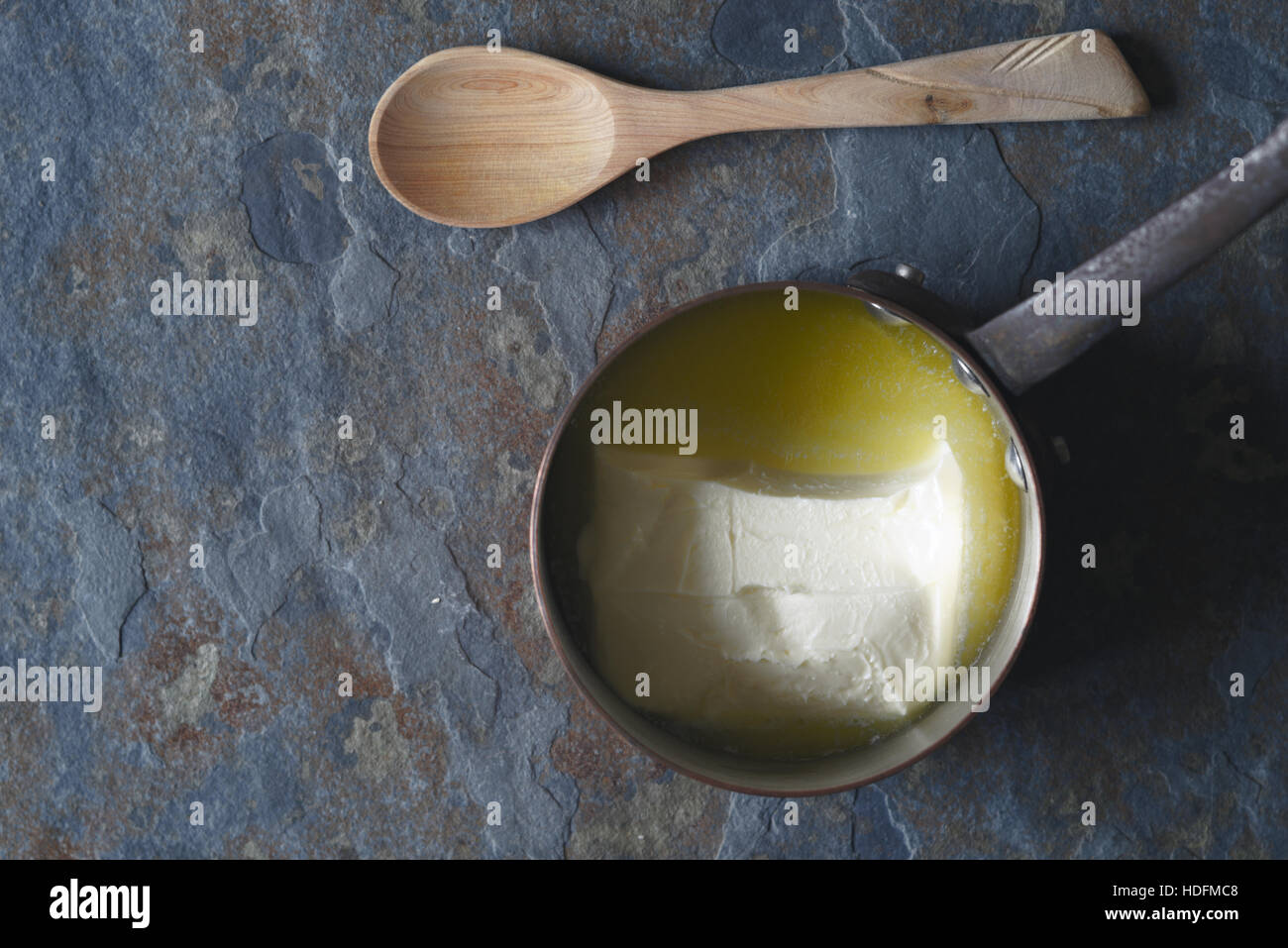 Melted butter in the stewpan on the stone background top view - Stock Image