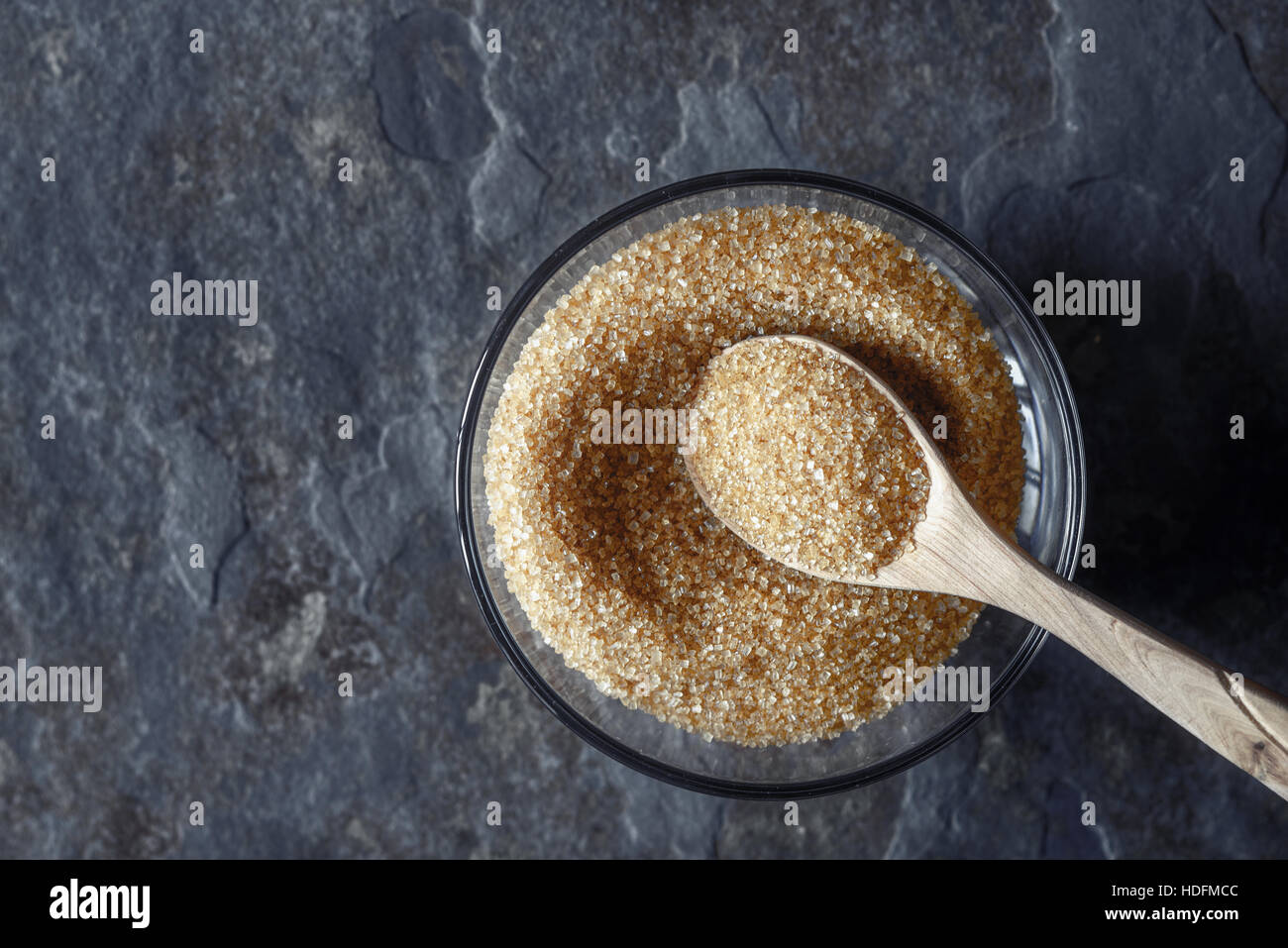 Brown sugar in the glass bowl on the stone background top view - Stock Image