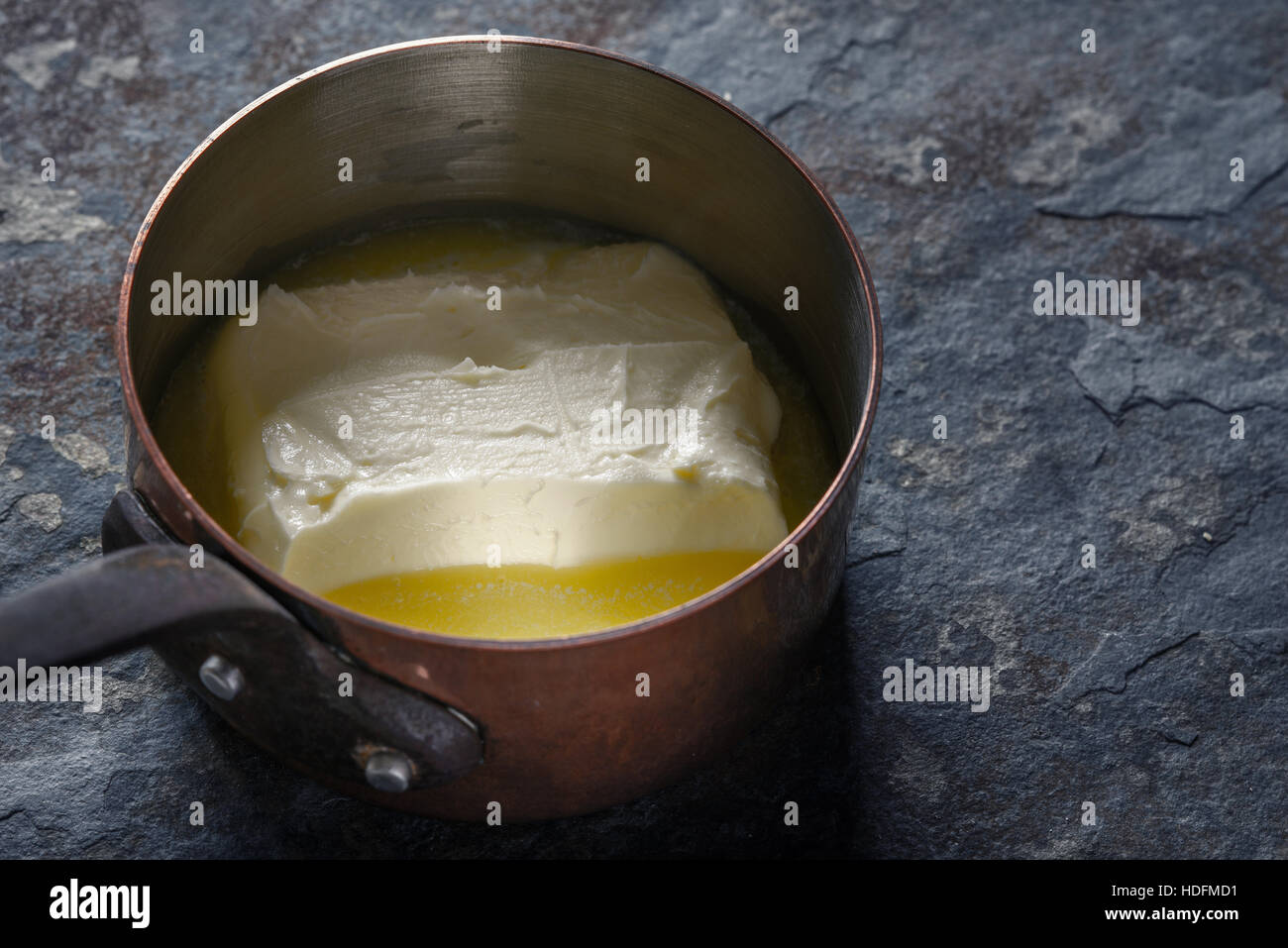 Melted butter in the stewpan on the stone background horizontal - Stock Image