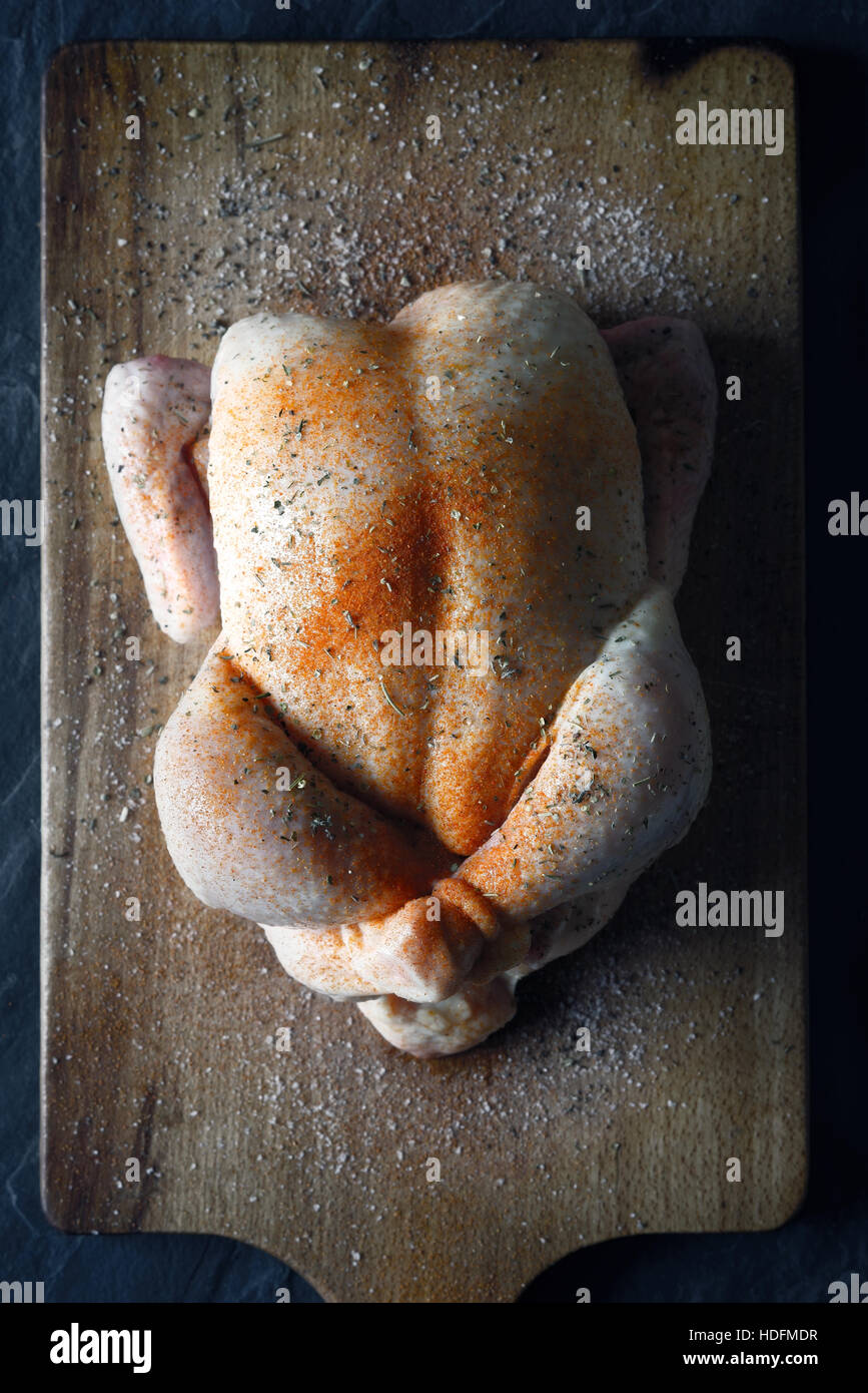Raw Thanksgiving day turkey with spices on the wooden board top view - Stock Image