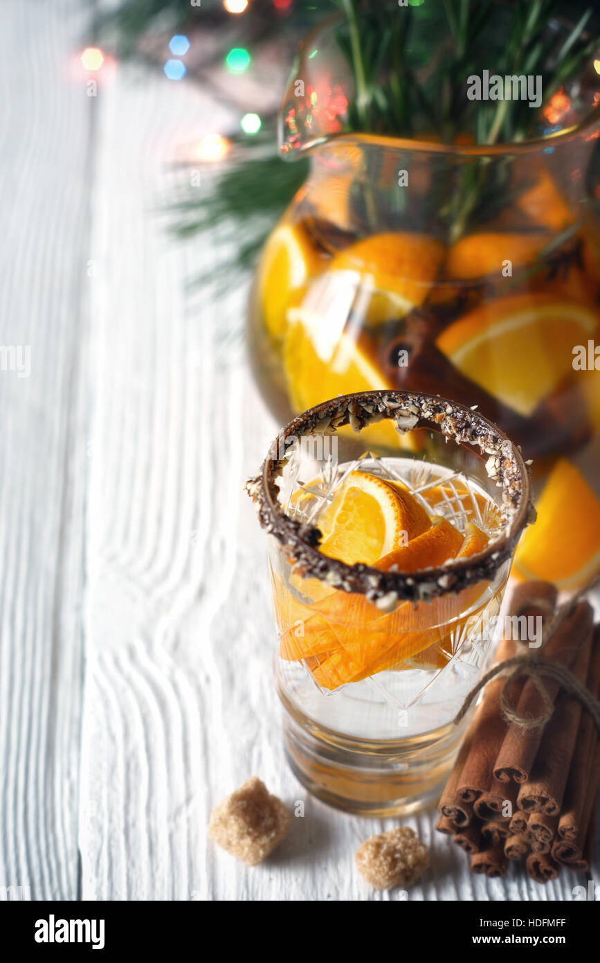 Citrus cocktail in the decorated glass on the white wooden table vertical - Stock Image