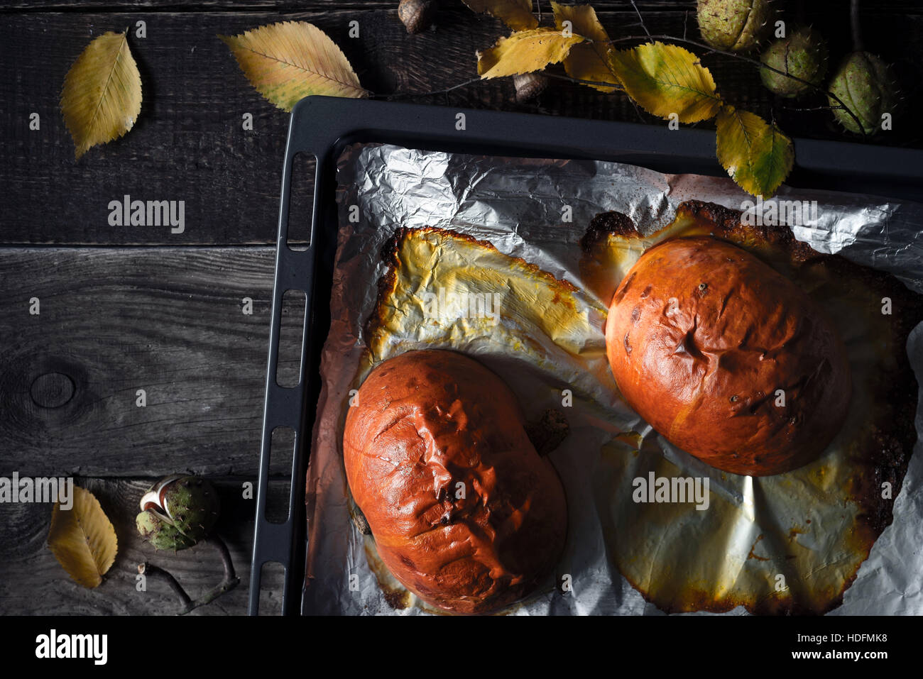 Halves of baked pumpkin on the baking tray on the wooden table top view - Stock Image