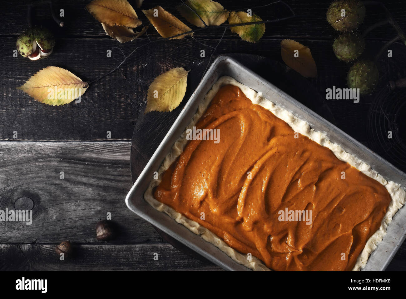 Raw pumpkin pie  on the wooden table top view - Stock Image