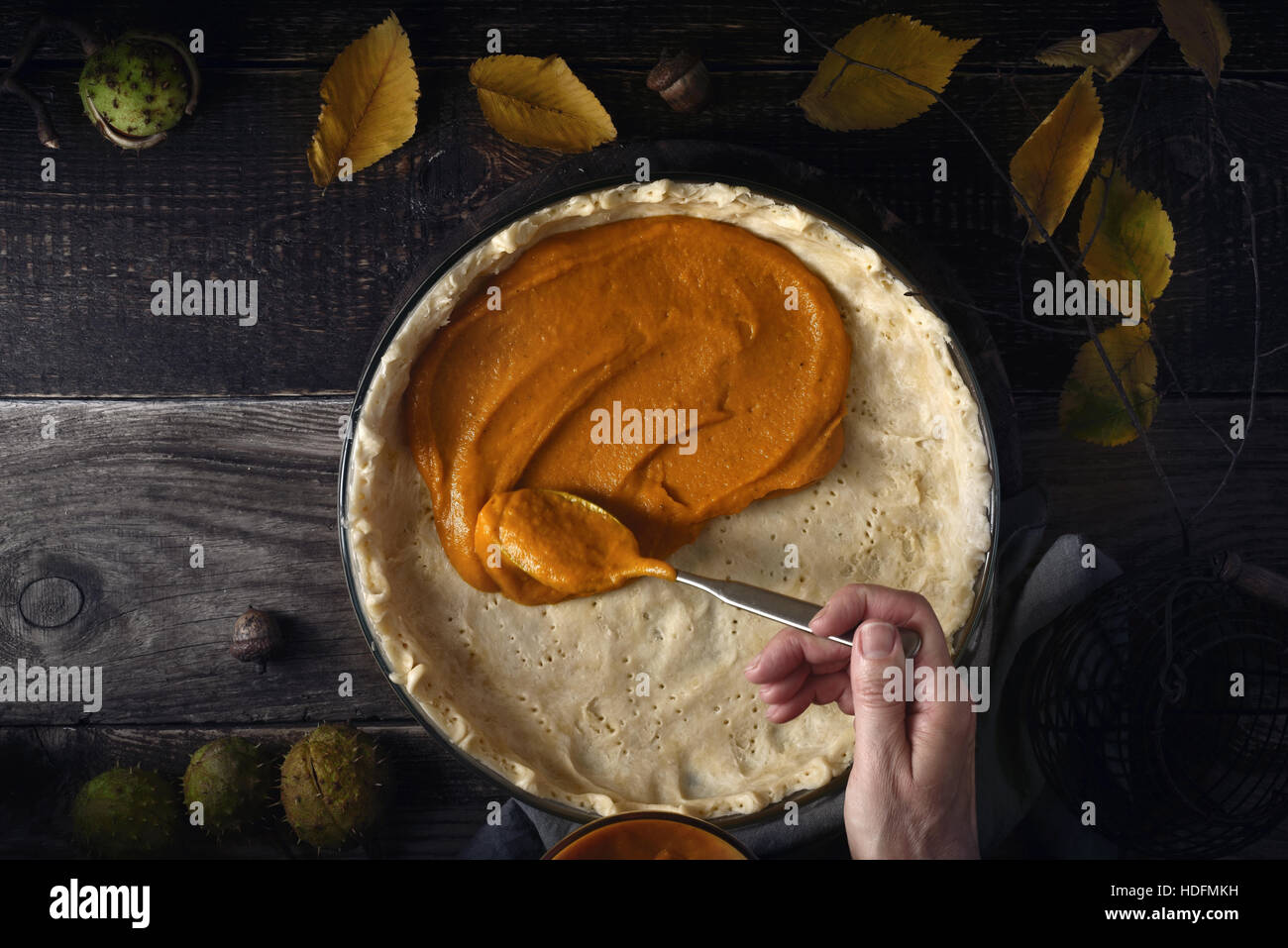 Putting  pumpkin puree on the dough for pumpkin pie on the wooden table - Stock Image