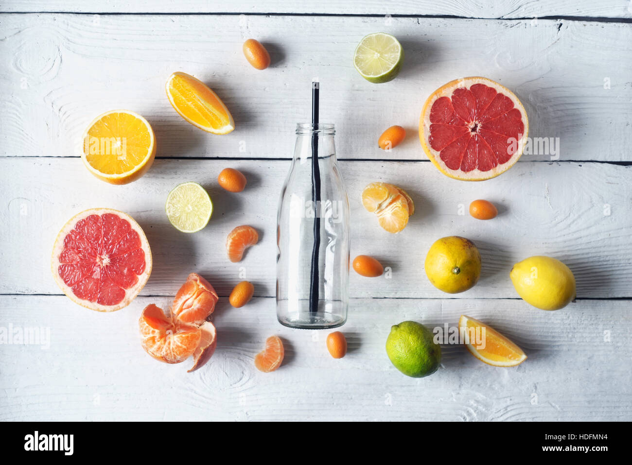 Glass bottle surrounded by different citrus on the white wooden table top view - Stock Image