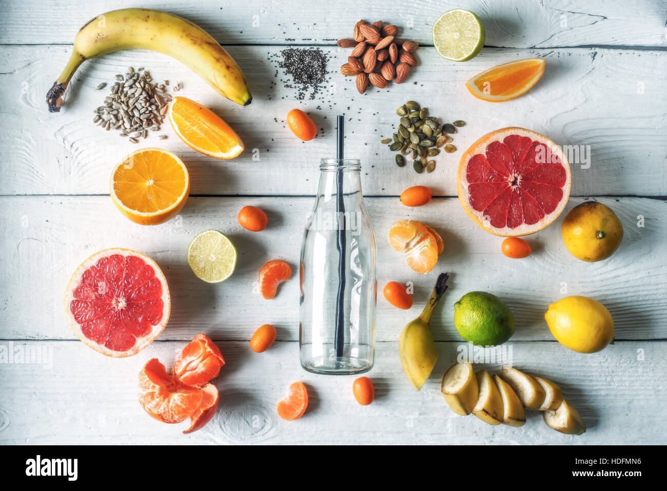 Glass bottle surrounded by different fruits and nuts on the white wooden table top view - Stock Image