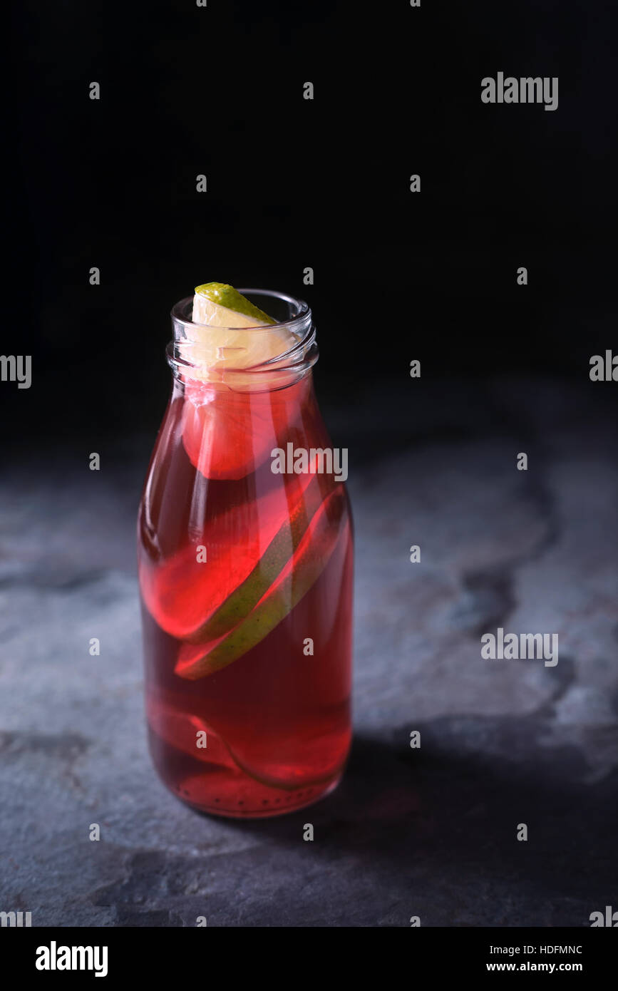 Glass bottle with citrus cocktail on the dark background vertical - Stock Image