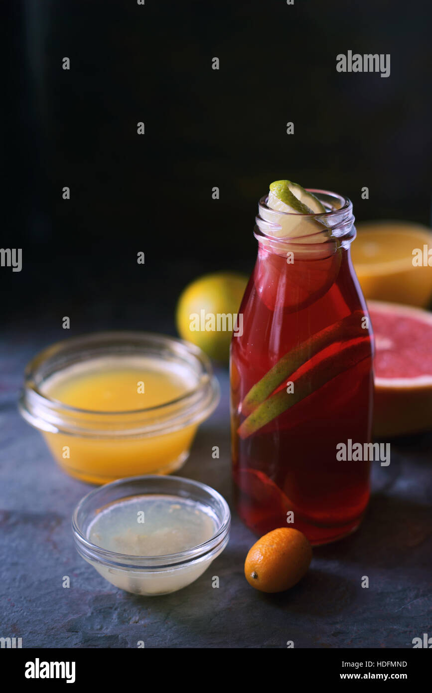 Glass bottle with citrus cocktail on the dark  stone background - Stock Image