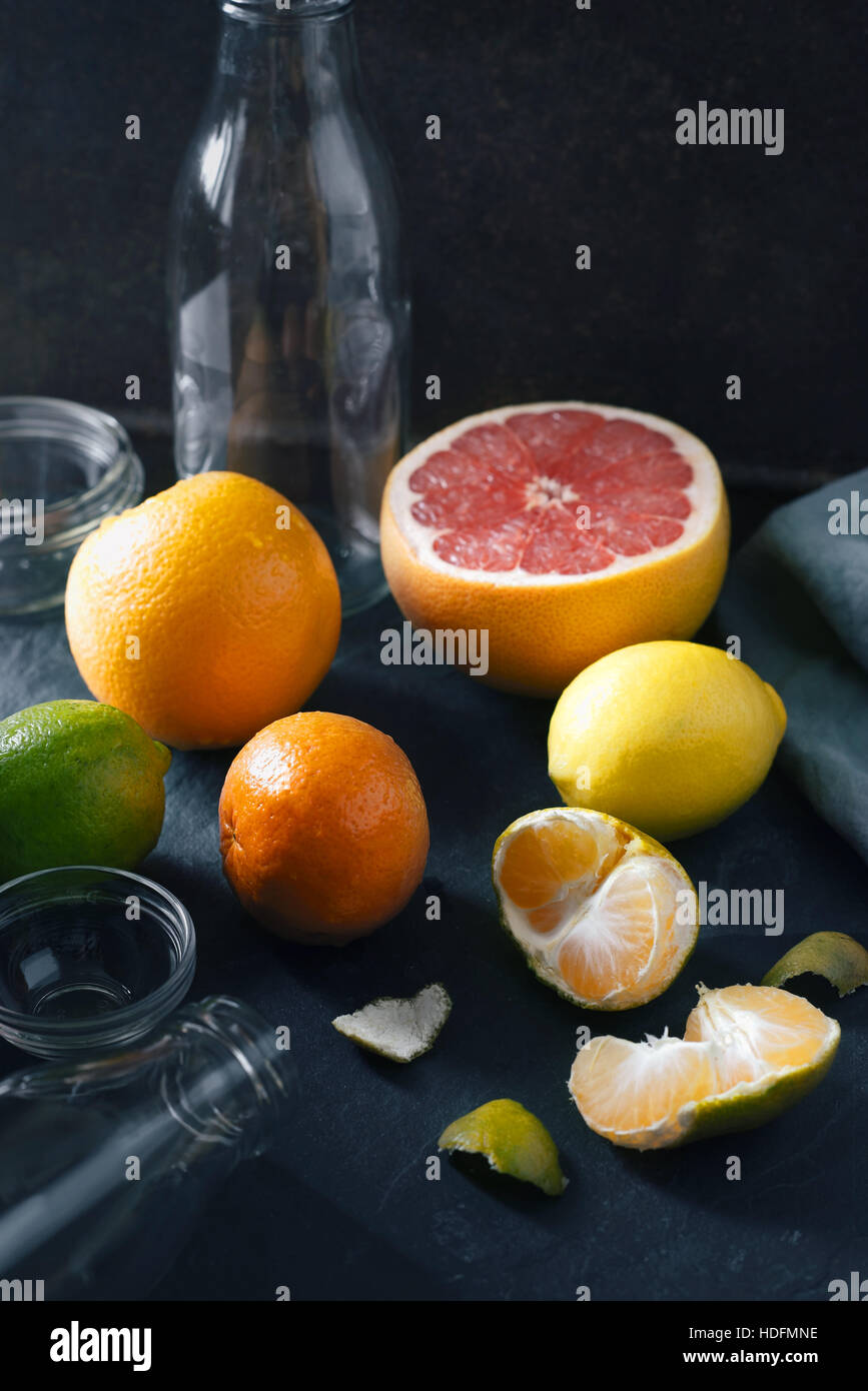 Citrus mix with empty glass bottle on the dark stone background - Stock Image