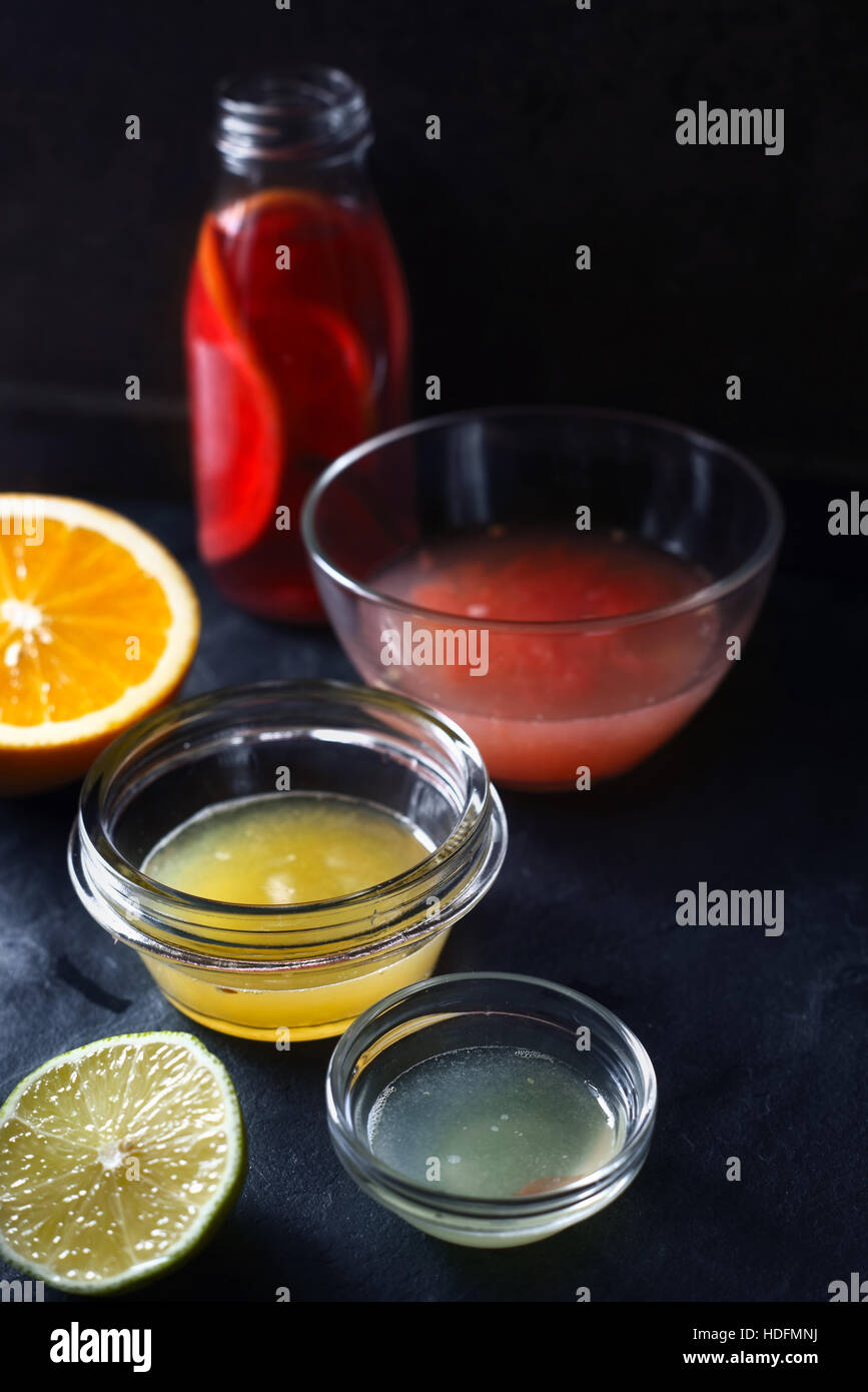 Citrus juice in the different glass bowl on the dark stone background - Stock Image