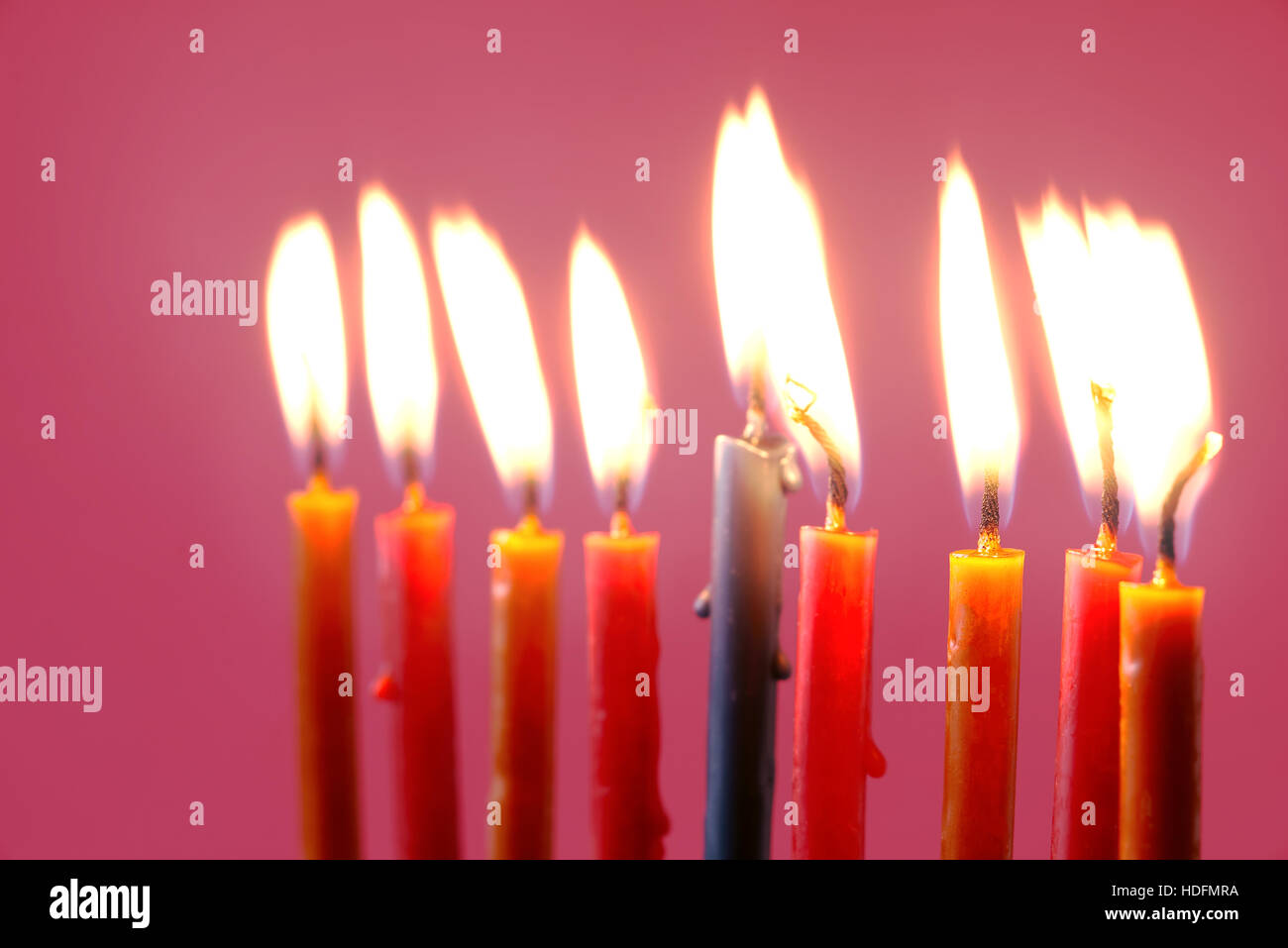 Hanukkah  burning candles on the pink background - Stock Image