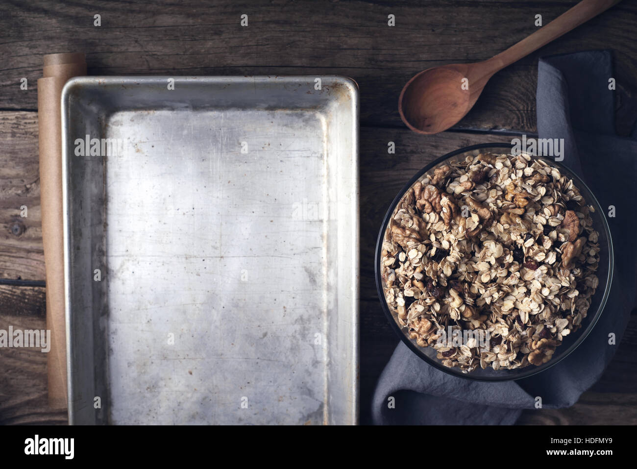 Granola in the glass bowl with baking tray on the wooden table top view - Stock Image