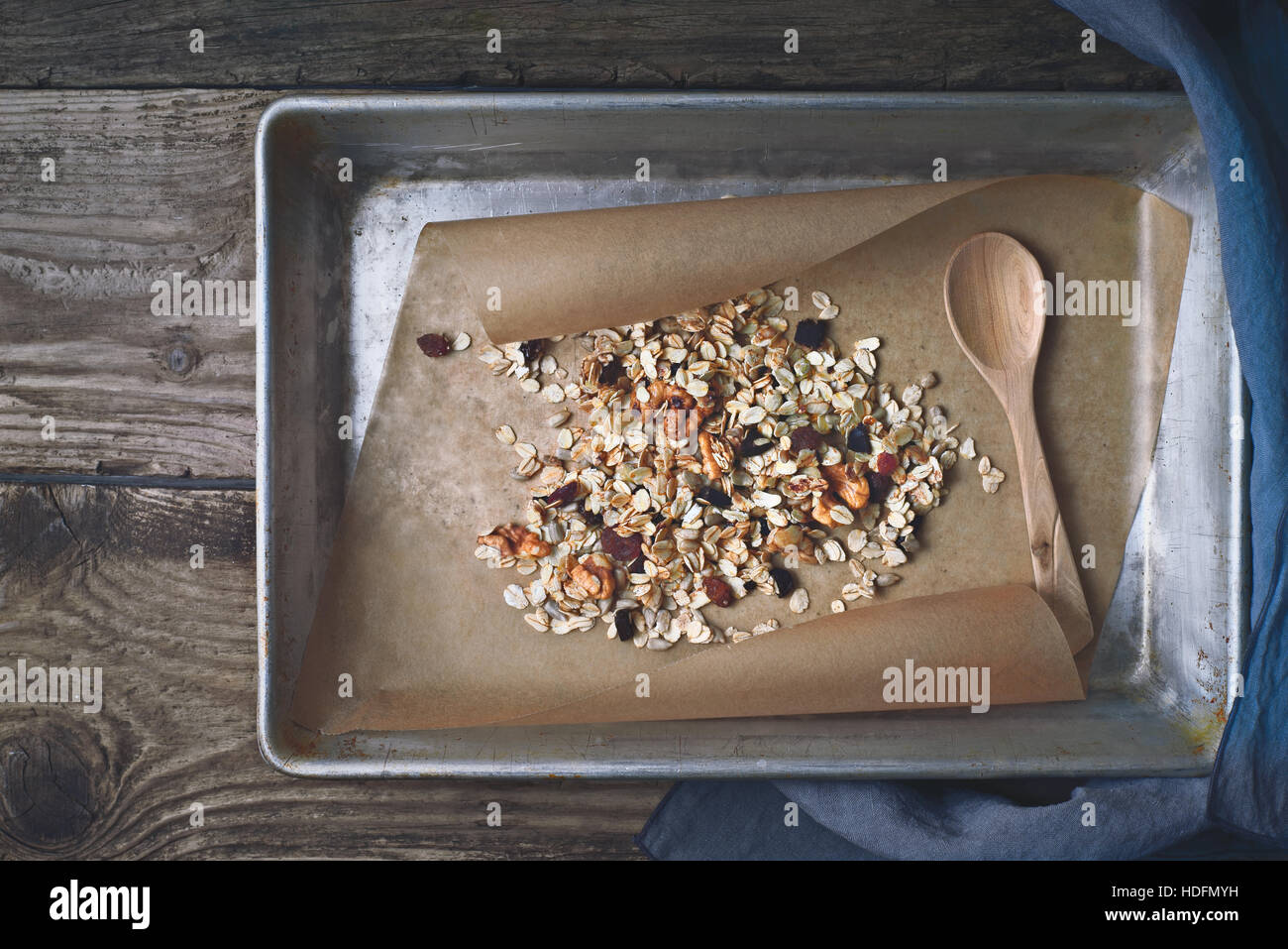 Granola in baking tray on the wooden table top view - Stock Image