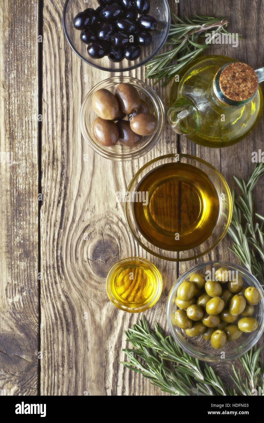 Olives with olive oil and rosemary on the wooden table - Stock Image