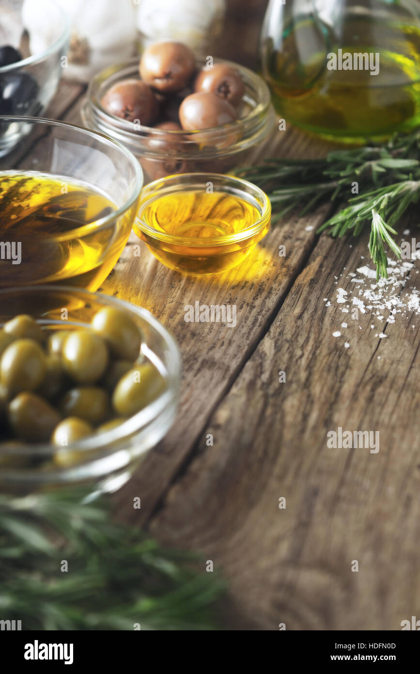 Olive oil  and olives on the wooden table  vertical - Stock Image