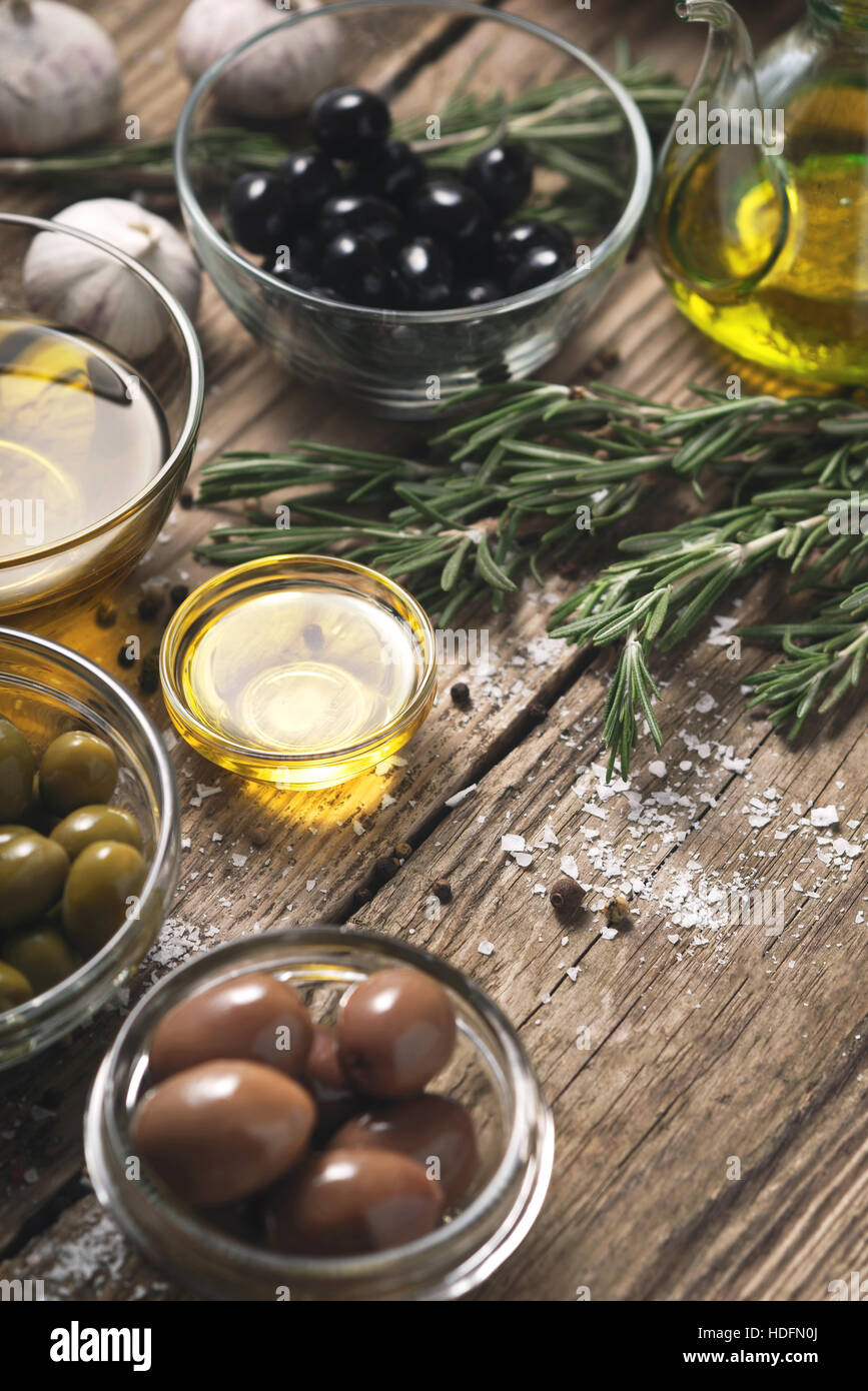 Olives with different seasoning on the wooden table - Stock Image