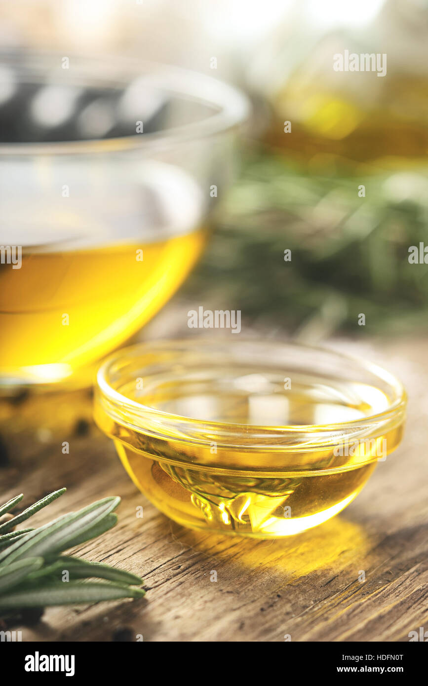 Olive oil  in the glass bowl on wooden table  vertical - Stock Image