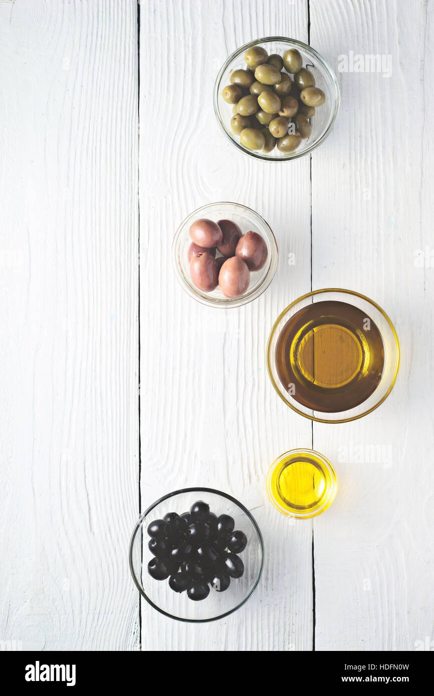 Different olives and olive oil on the white wooden table top view - Stock Image