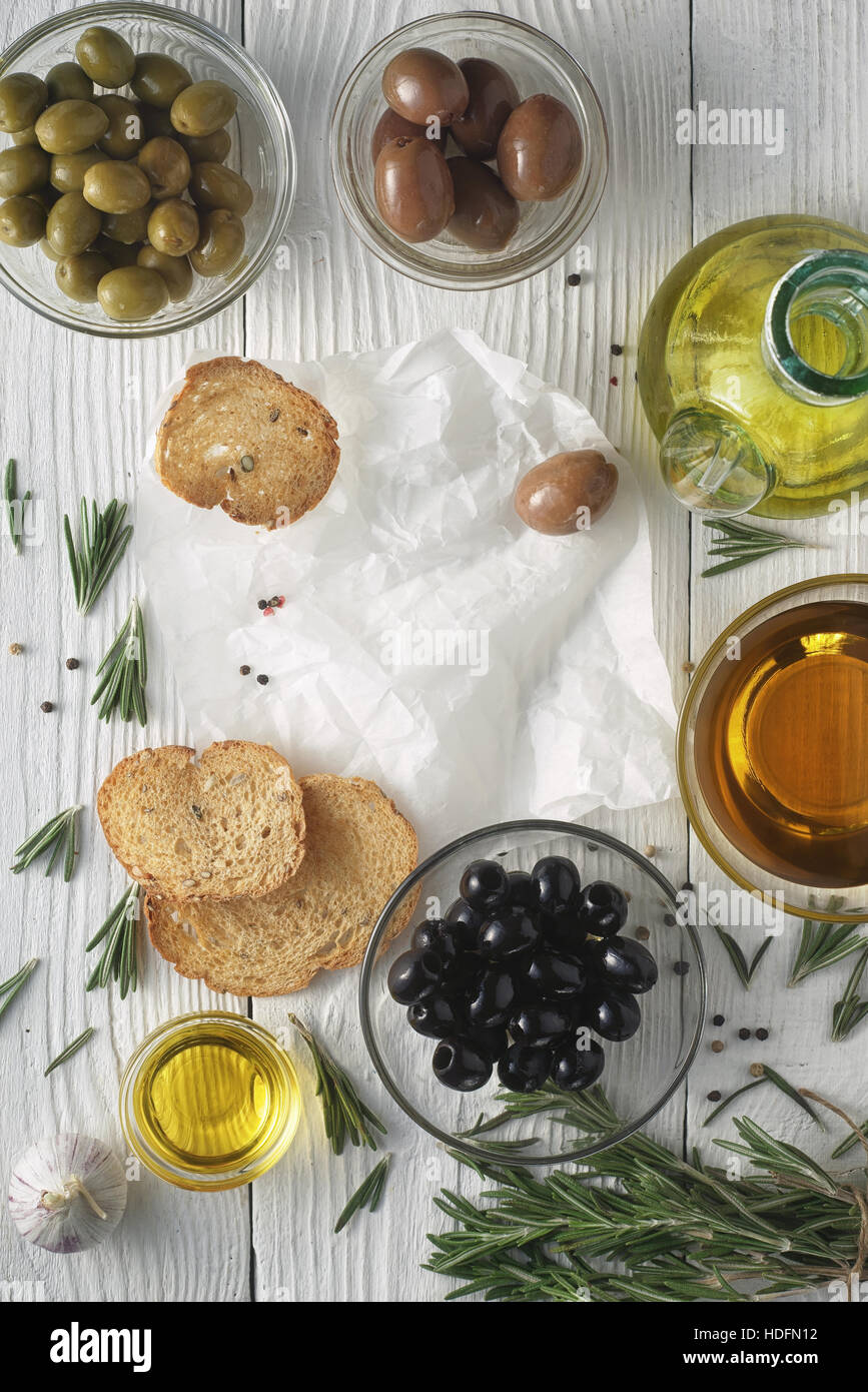 Olive oil with  bread and olives mix on the white wooden table vertical - Stock Image