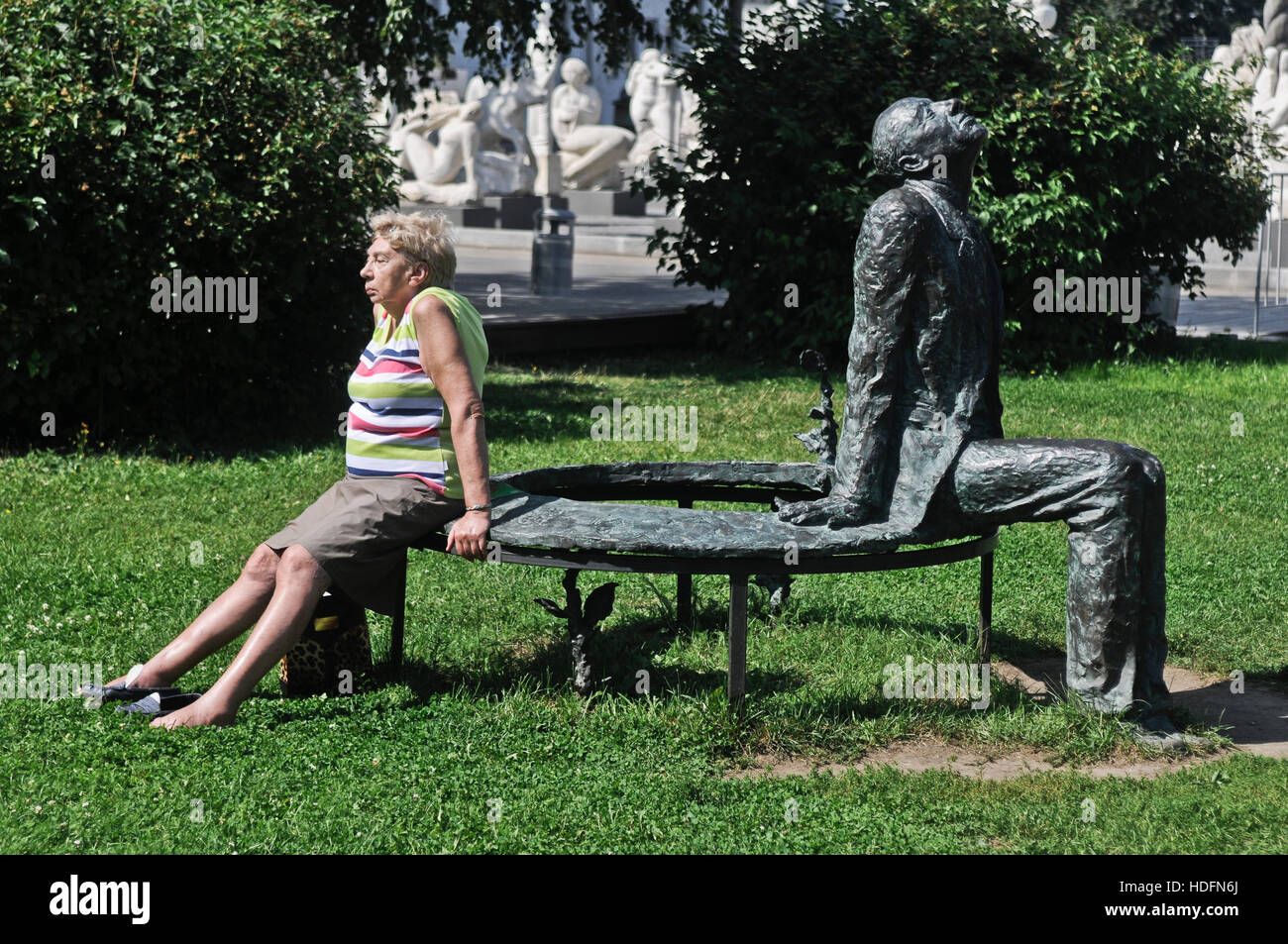 Russian old woman sitting beside a statue, with identical symmetric position and posture - Stock Image