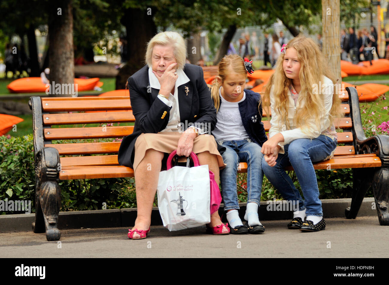 Russian grandmother with grandchildren sitting on a bench, looking sad. Gorki Park, Moscow, Russia Stock Photo