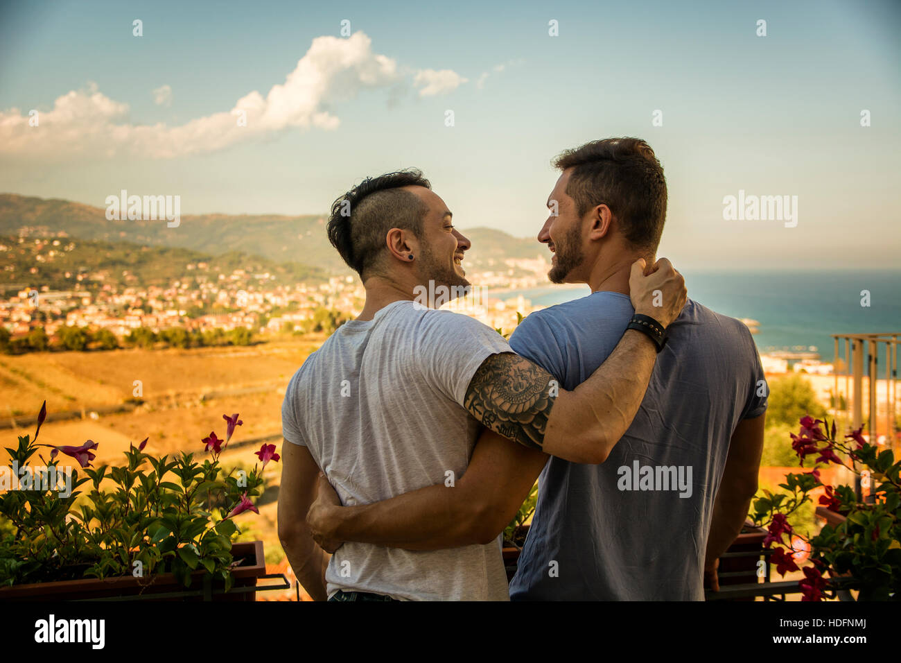 Back view of homosexual couple embracing nd looking at each other on background of resort. - Stock Image