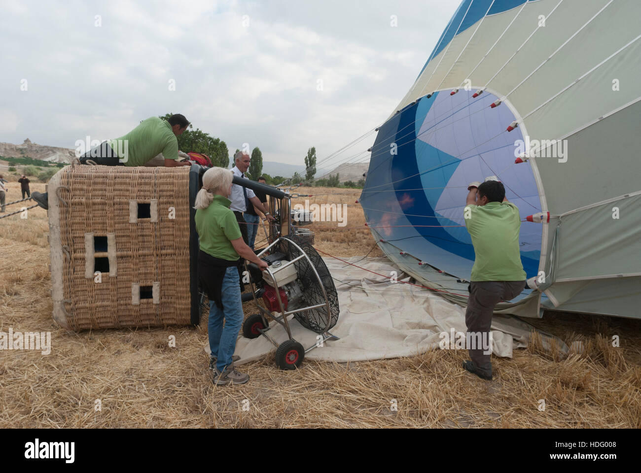 Ground crew preparing a hot air balloon for launch with a propane burner and power fan. - Stock Image