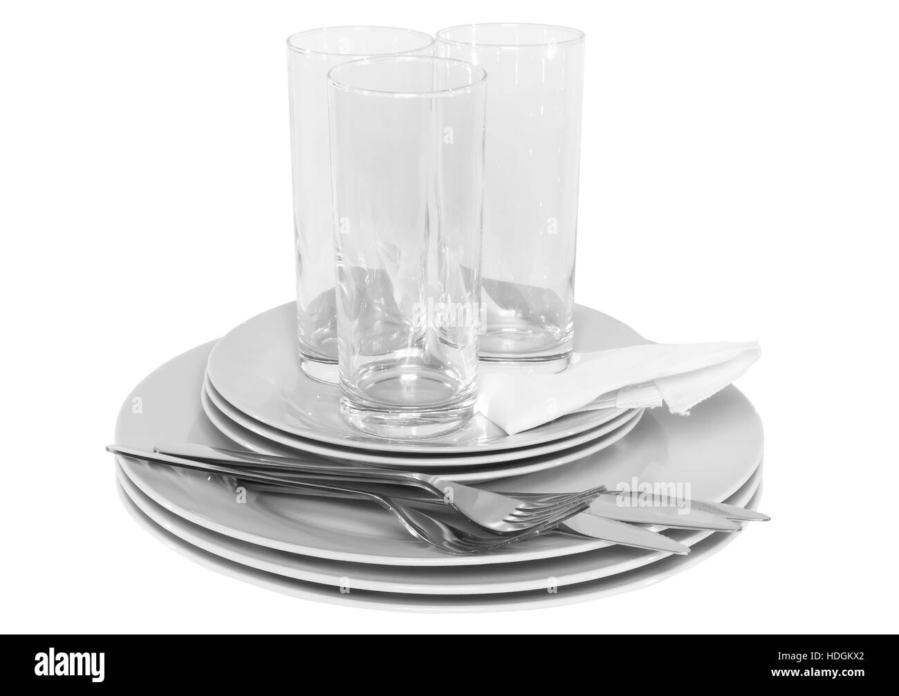 Pile of white plates, glasses with forks and spoons on silk napkin. Isolated over white - Stock Image