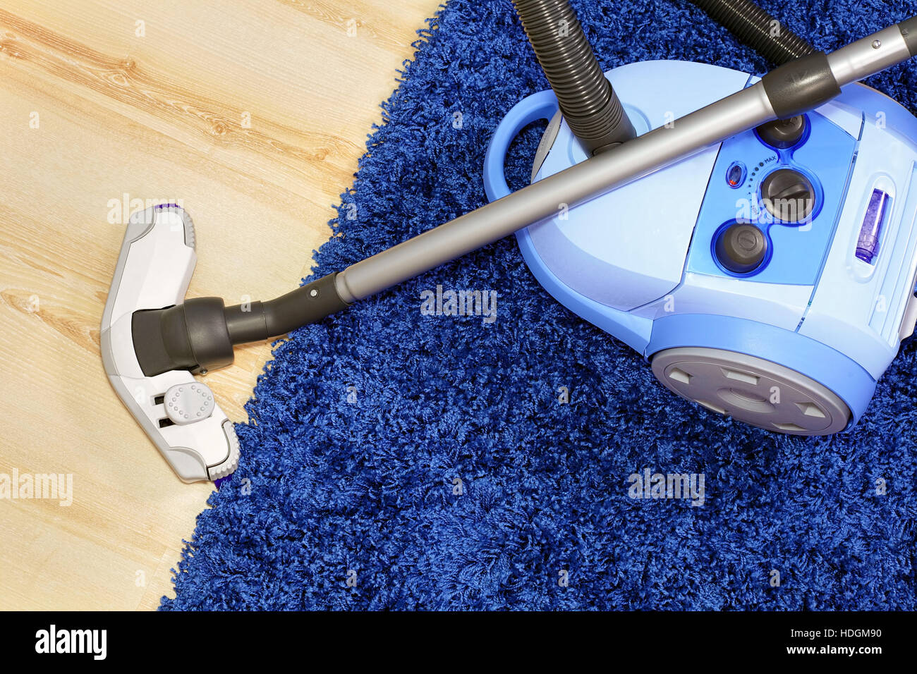 Powerful vacuum cleaner stand  on blue carpet. - Stock Image