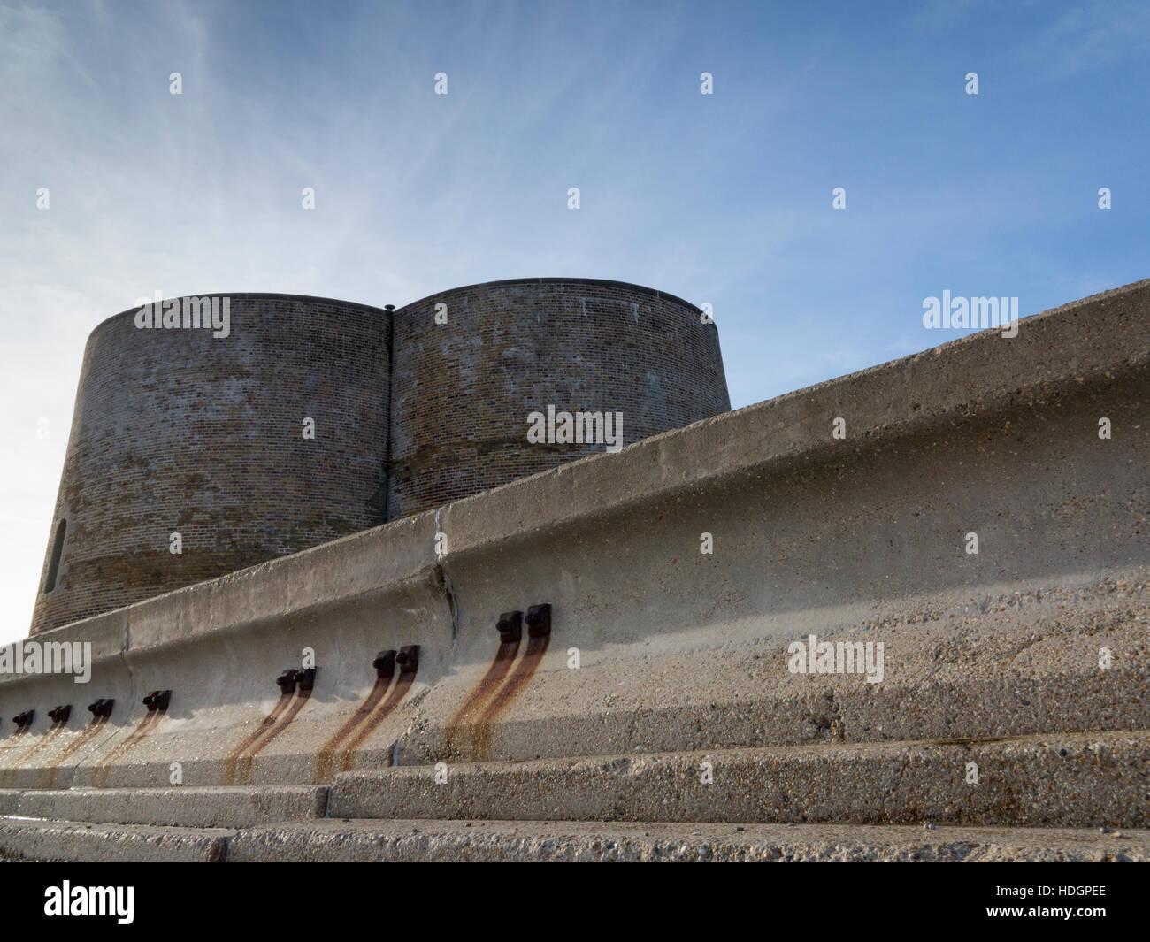 Martello towers behind concrete sea wall defense, Aldeburgh, Suffolk,England - Stock Image