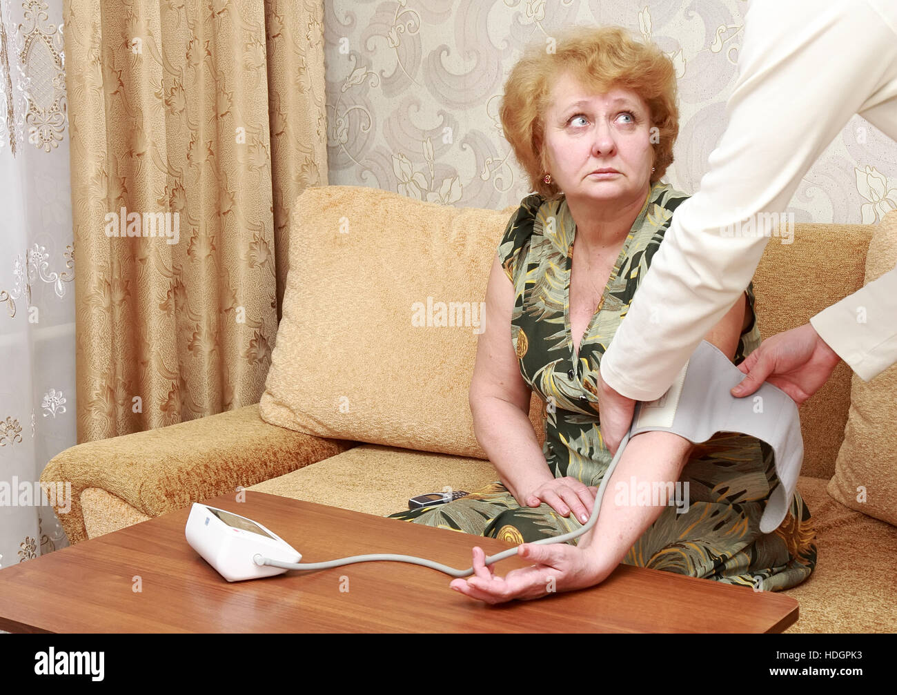 Old woman measures arterial pressure , with doctor helps. - Stock Image