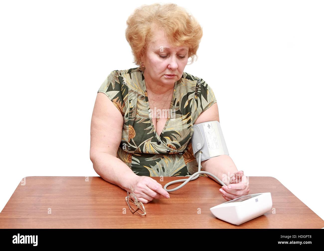Senior lady measures arterial pressure , use digital tonometer . Isolated. - Stock Image