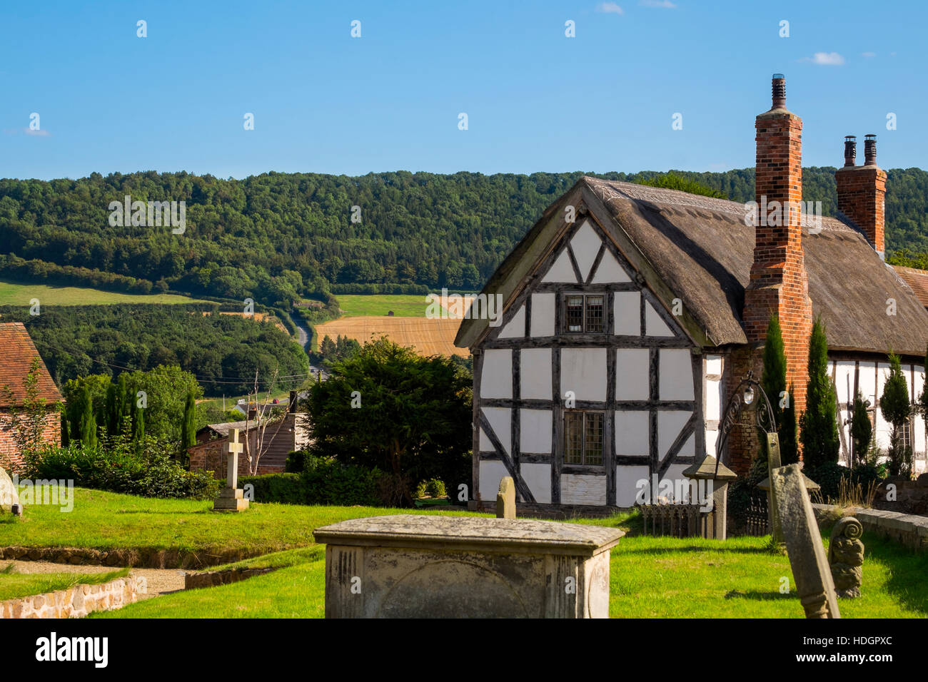 Black and White thatched cottage at Harley, Shropshire, with Wenlock Edge in the background, England, UK - Stock Image