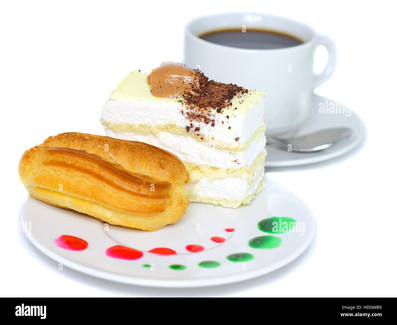 Sponge cakes and eclair cake on plate with fruit juice spots. Isolated - Stock Image