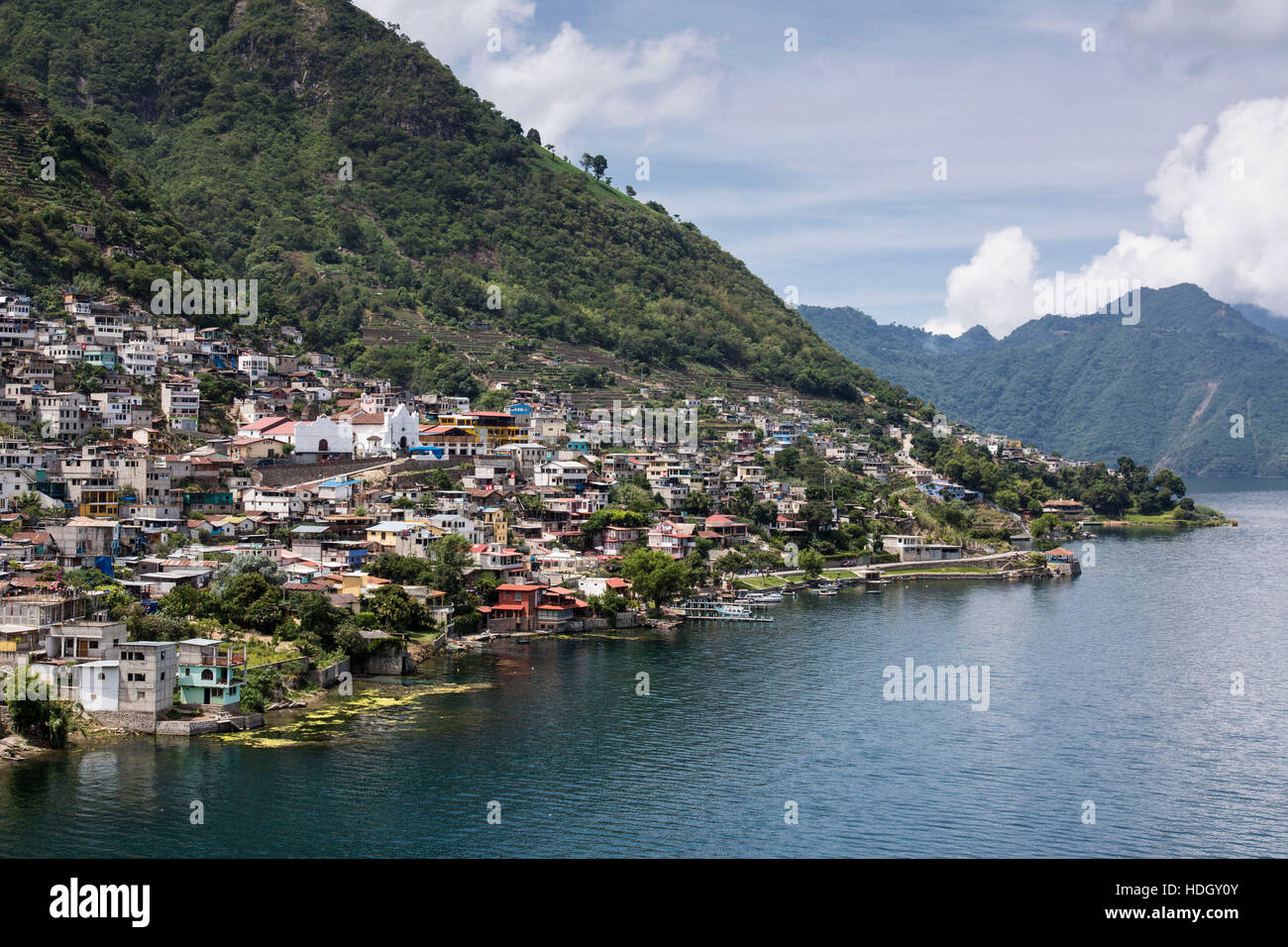 Distant view of San Antonio Palopo, Guatemala, on the shore of Lake Atitlan.  Steep hillsides drop into the lake, which is an extinict volcanic crater Stock Photo
