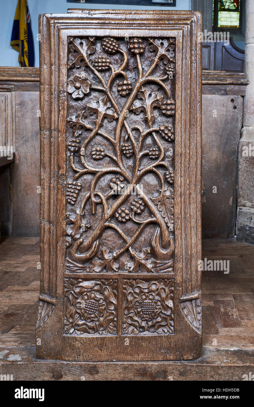 Crowcombe church, Somerset. Wooden 1530s bench end with elaborate carving of floral; geometric and religious designs. - Stock Image
