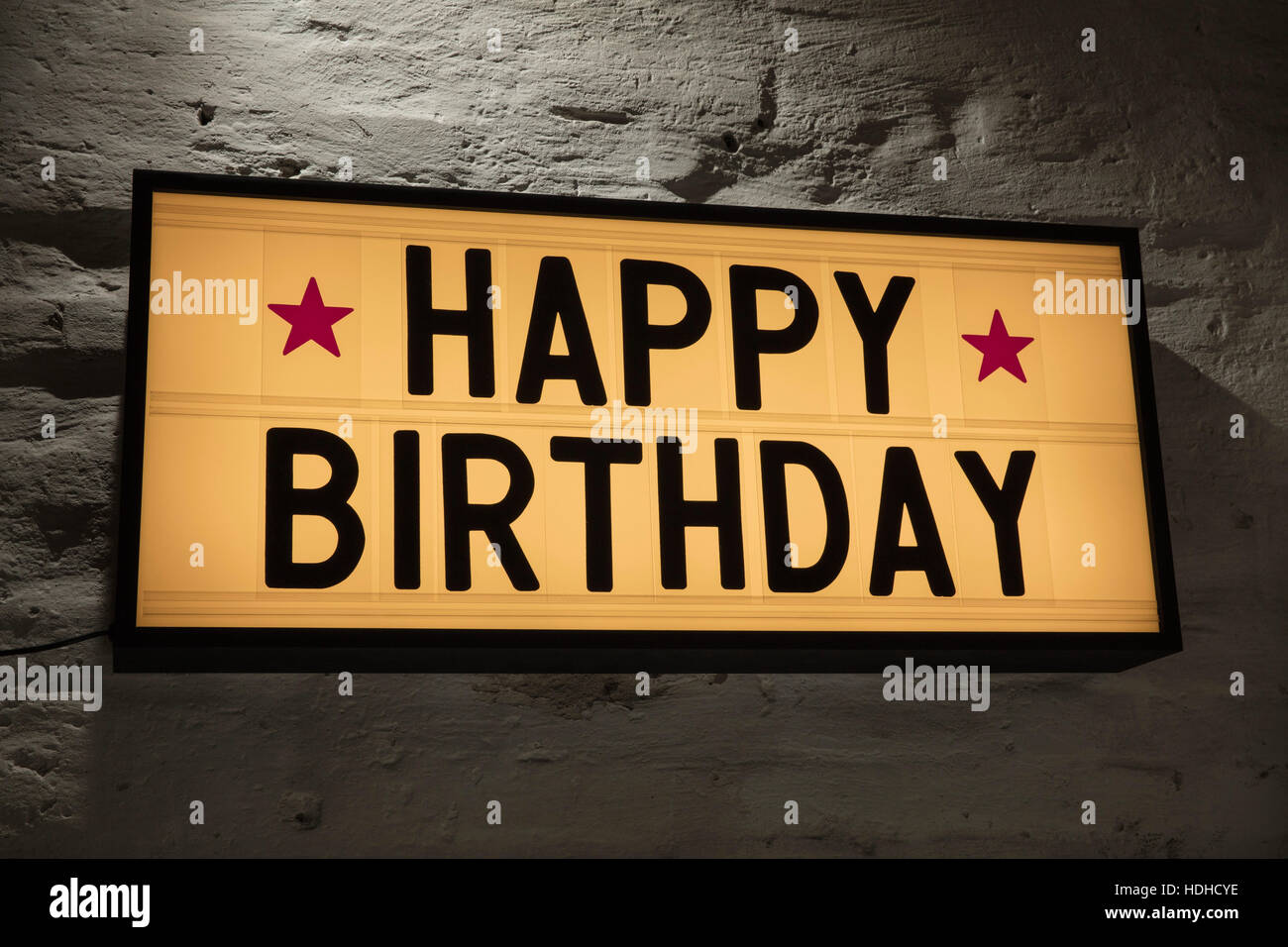 close up of happy birthday signboard against gray wall stock photo