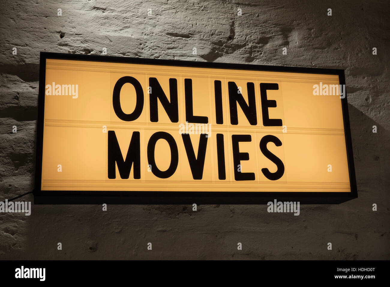 Close-up of Online Movies signboard against gray wall - Stock Image