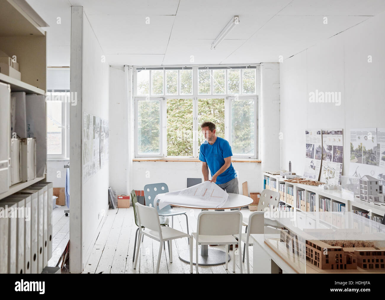 A modern office. A man looking at plans at a table, architectural drawings. Building models on shelves. Open windows. - Stock Image