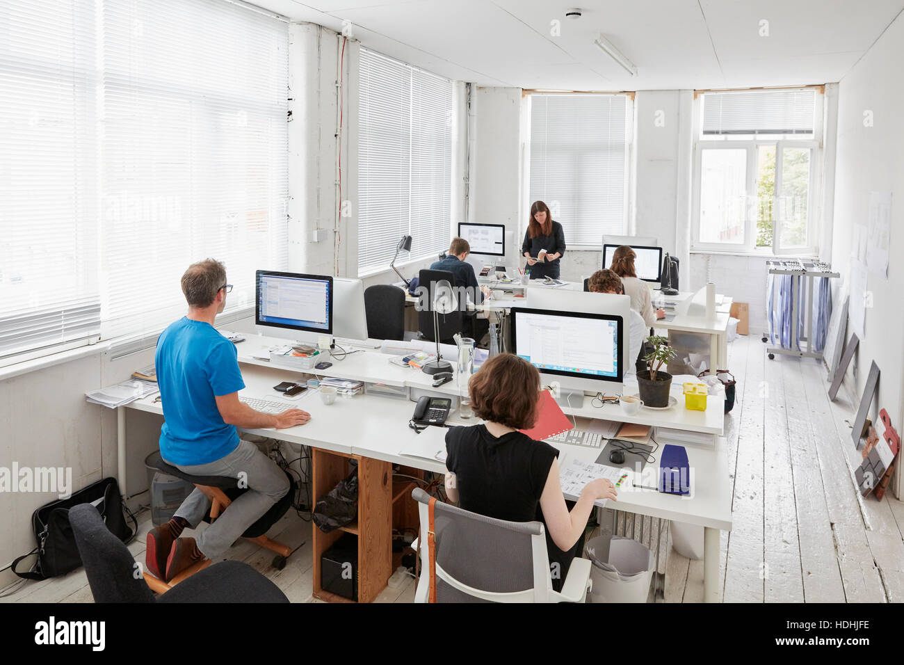 A modern office, workstations for staff. Elevated view of six people seated at desks. A man using an ergonomic kneeler - Stock Image