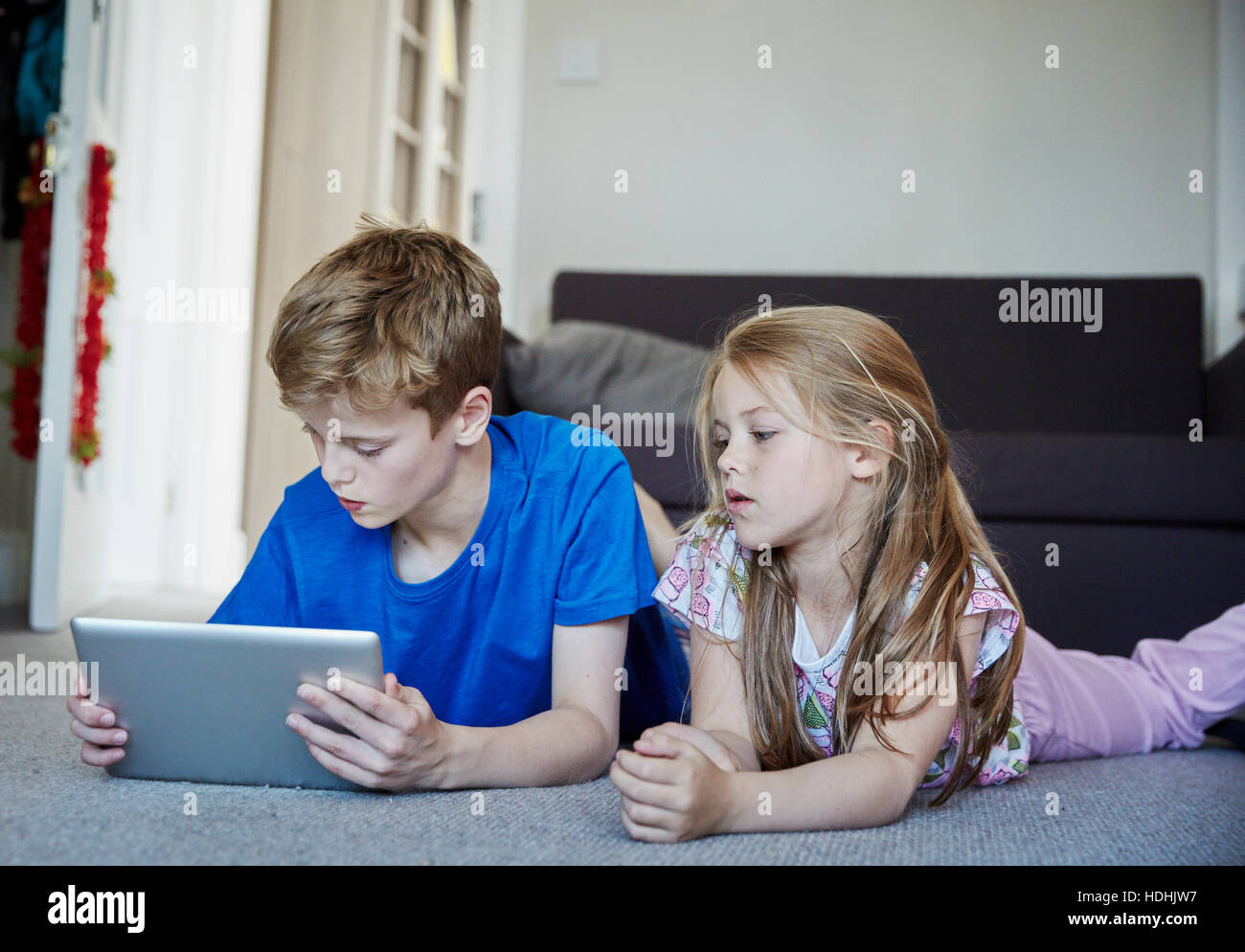 Two children lying on their stomachs sharing a digital tablet watching the screen. - Stock Image