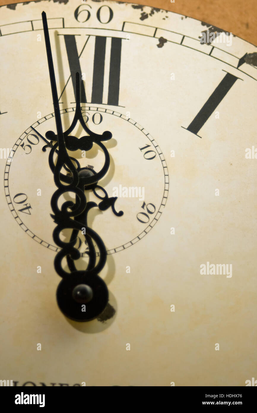 Clock face with ornate hands and time approaching twelve o'clock. - Stock Image