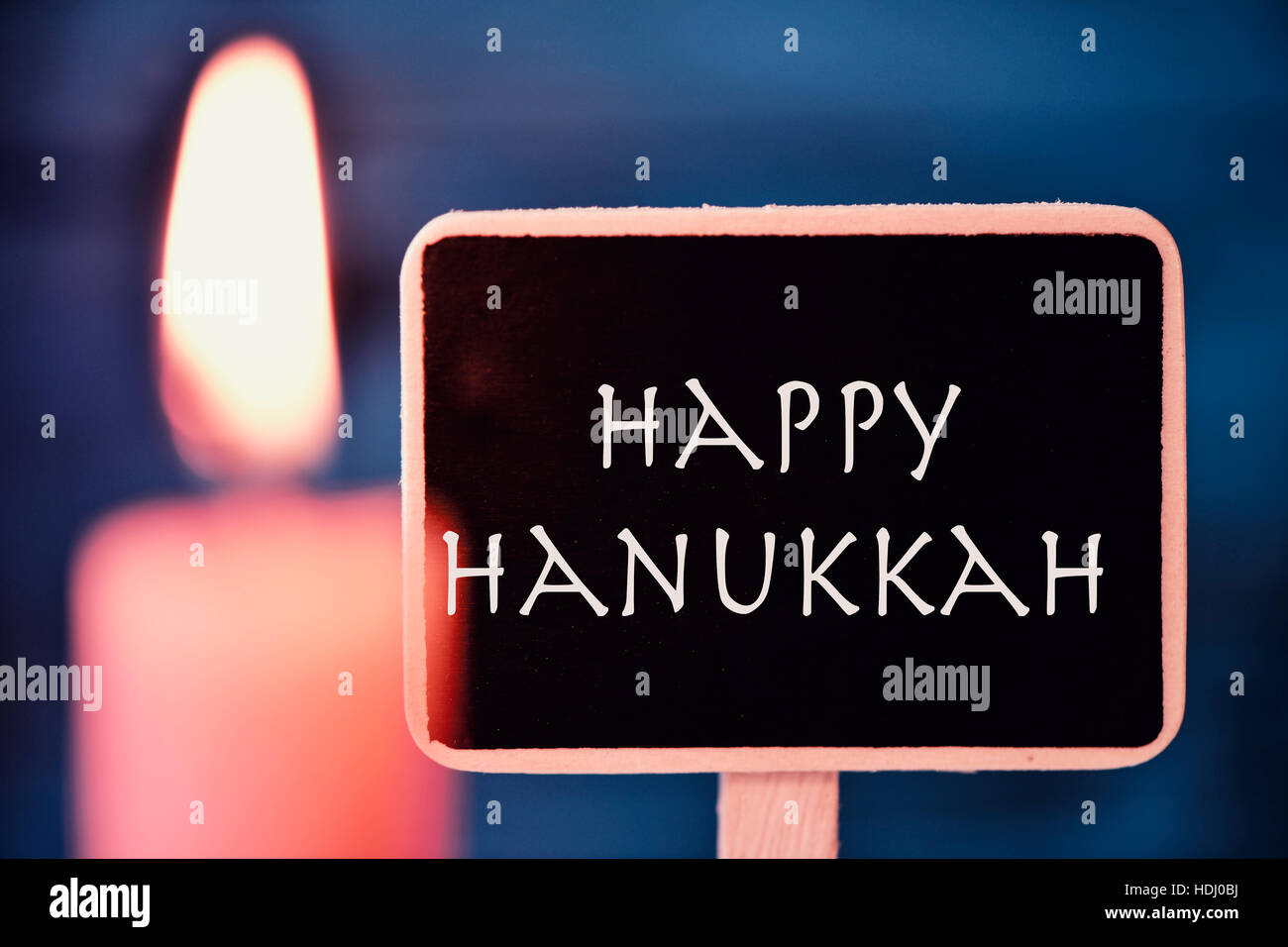 closeup of a black signboard with the text happy Hanukkah, for the Jewish Festival of Lights, and a lit candle - Stock Image