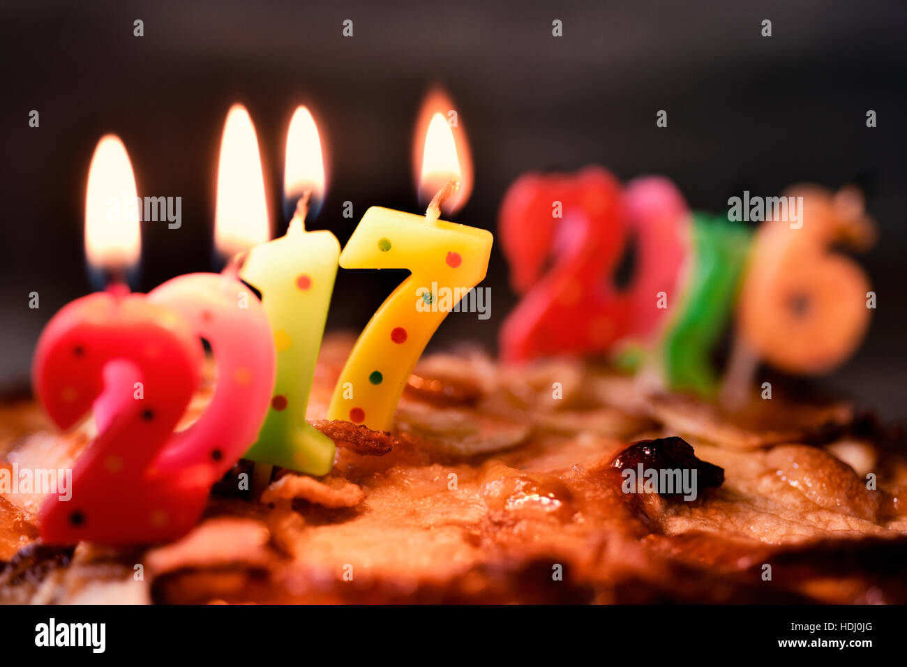 four lit number-shaped candles of different colors forming the number 2017, as the new year, on a cake, and more - Stock Image