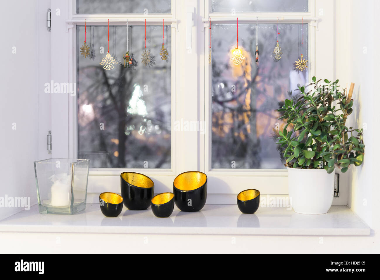 Candles on a window ledge with christmas lightning - Stock Image