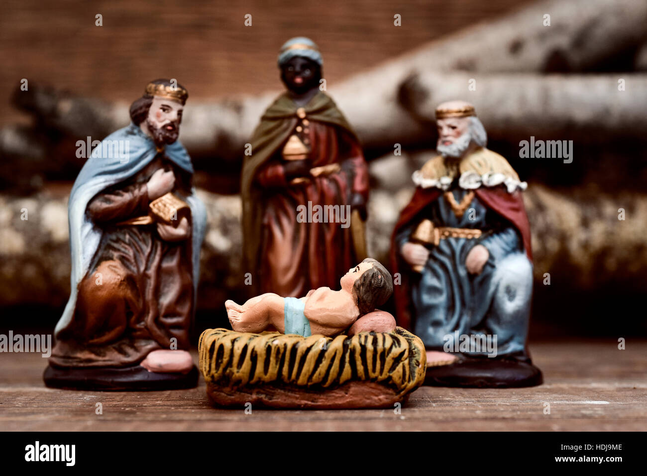 closeup of the three kings carrying their gifts adoring the Child Jesus on a rustic scene - Stock Image