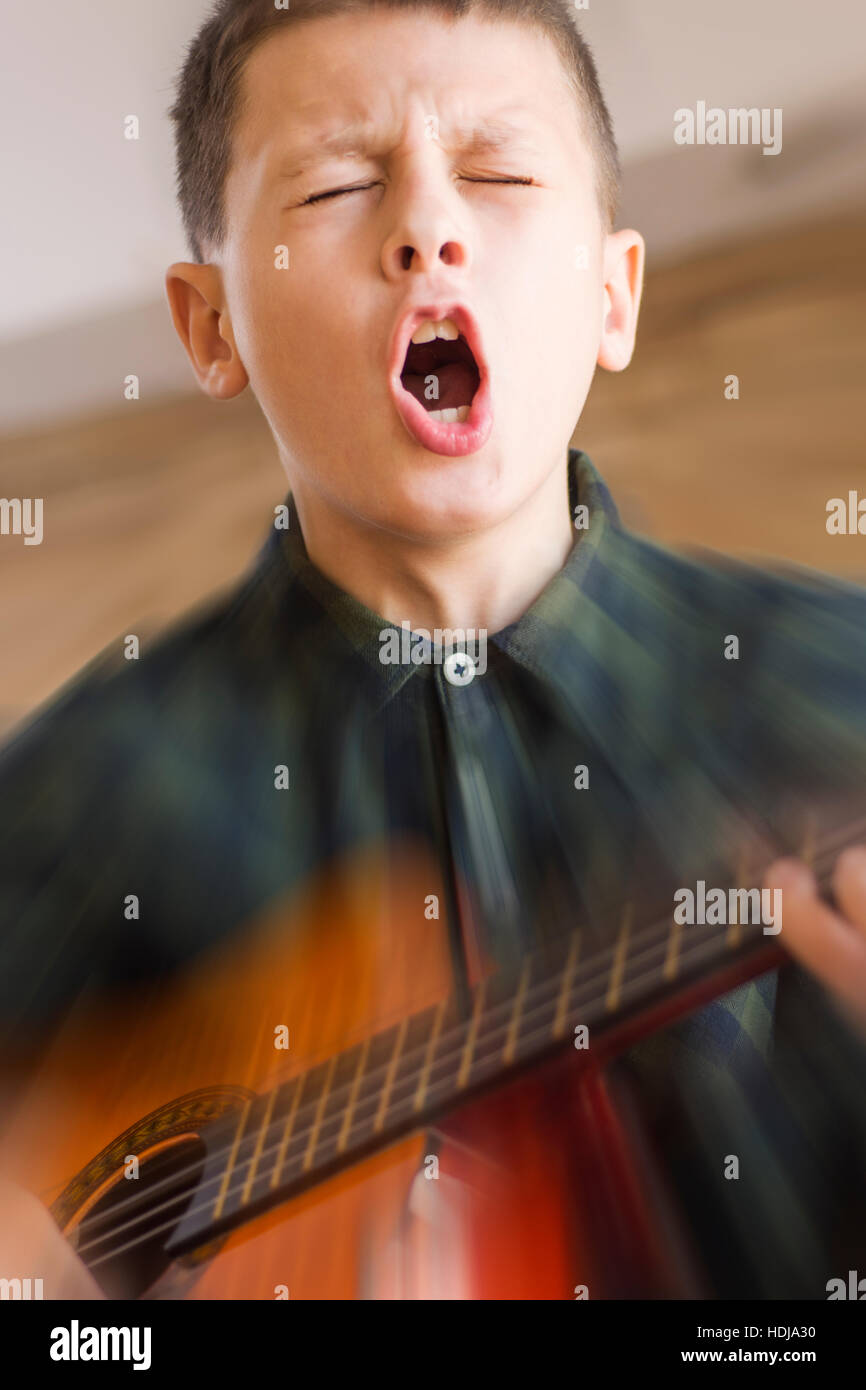 Young Boy Singing Out Loud While Playing Acoustic Guitar in Living Room - Stock Image