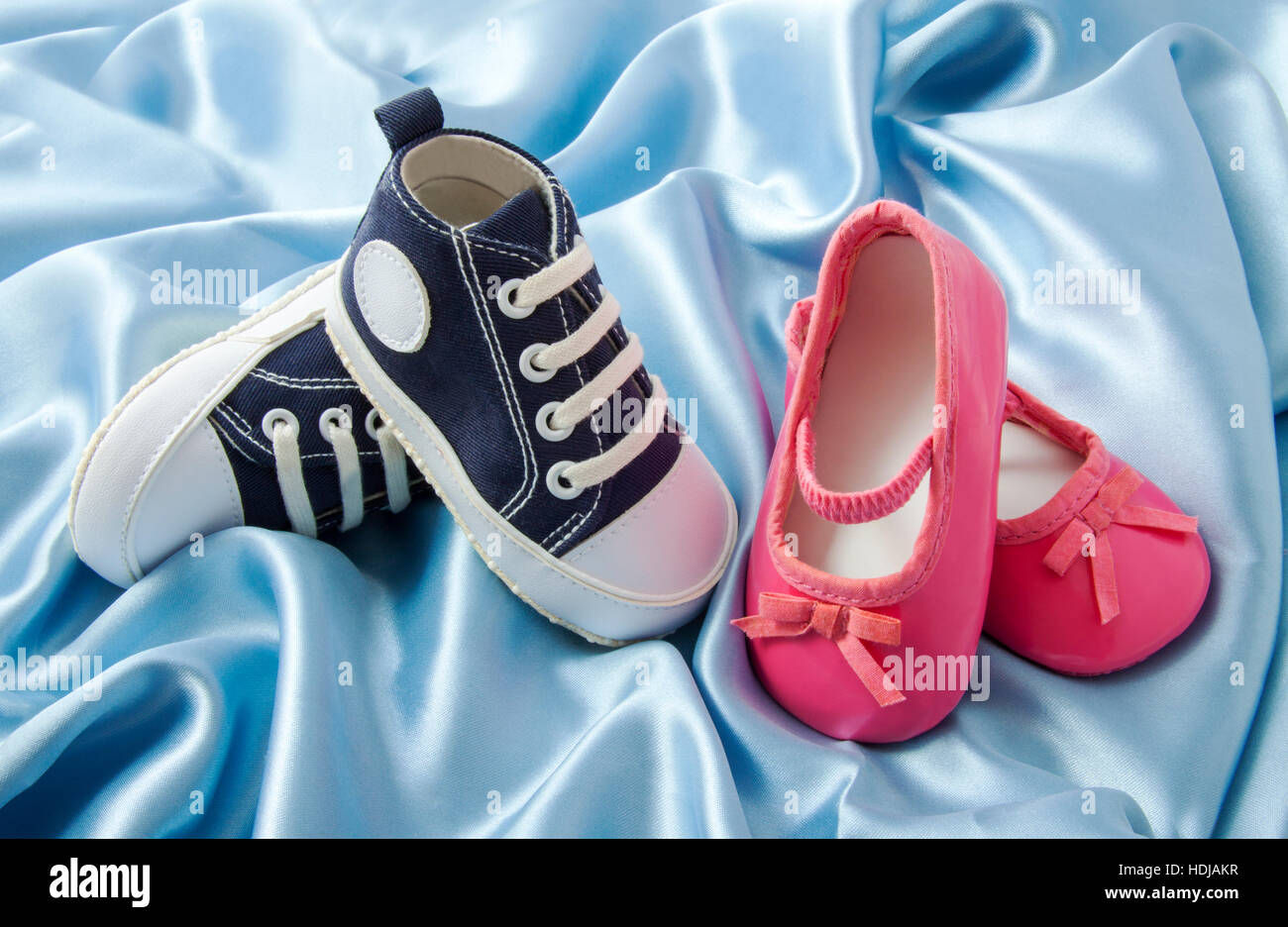 Blue baby sneakers and little pink ballet baby shoes on blue satin - Stock Image