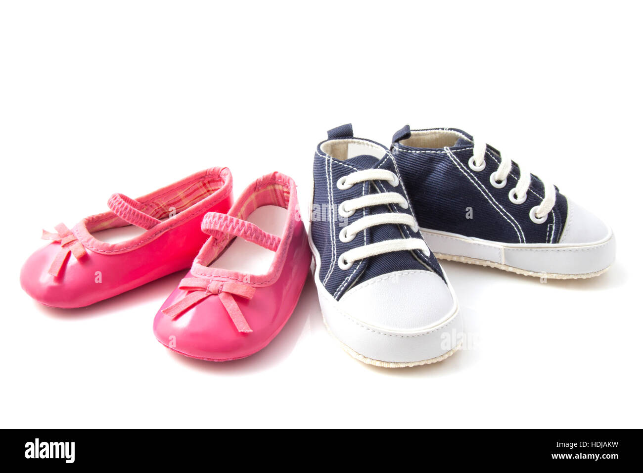 Pink baby ballet shoes and blue baby sneakers isolated over white - Stock Image